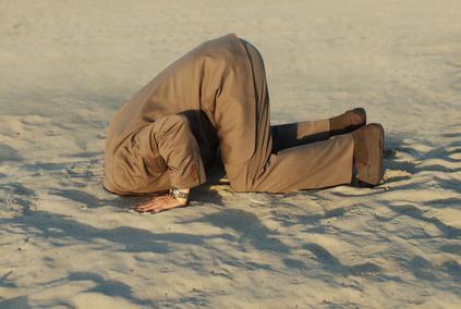 Hombre con la cabeza en la arena